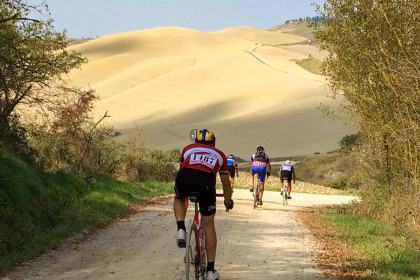 Riders descending the hills of the Val d'orcia in Tuscany during eroica