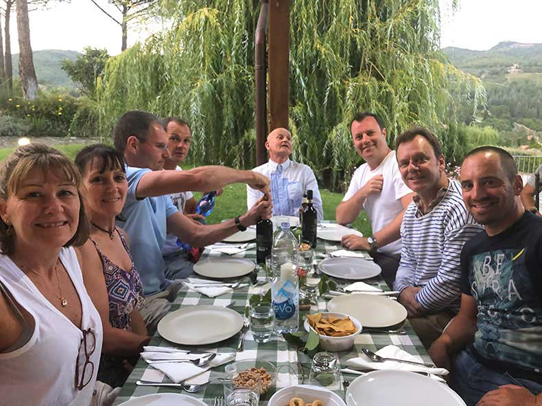 A group of poeple enjoying a dinner in Tuscany