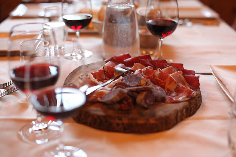 glasses of red wine and a mixed salumi board