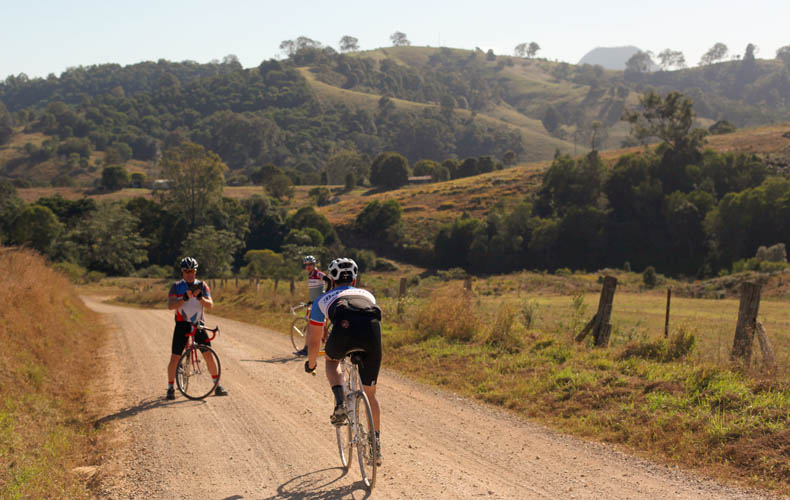 A riders cycling on steel bikes on a gravel road near Noosa