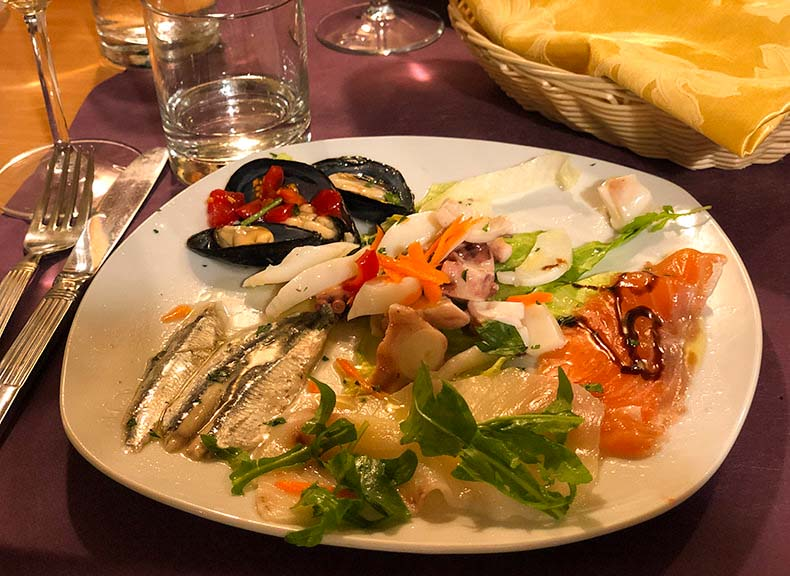 A glass of wine and a plate of mixed seafood antipasto
