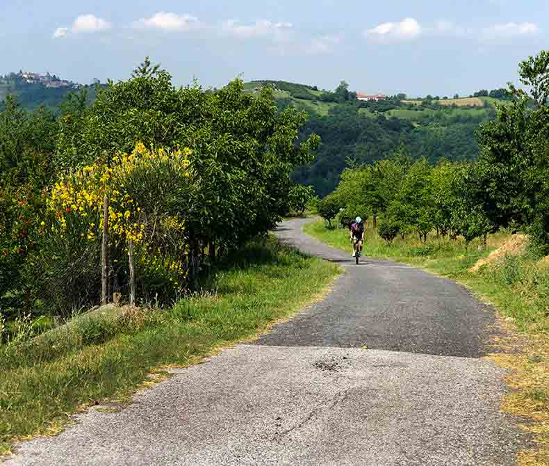 A man riding in the lush green landscape of Piemonte
