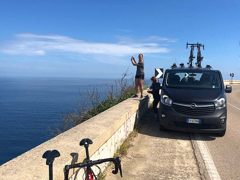 A lady taking a photo off the ocean beside the tour support van