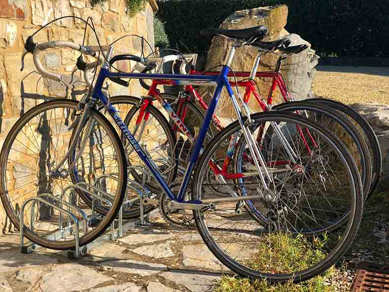Vintage steel bikes against a stone wall in Tuscany
